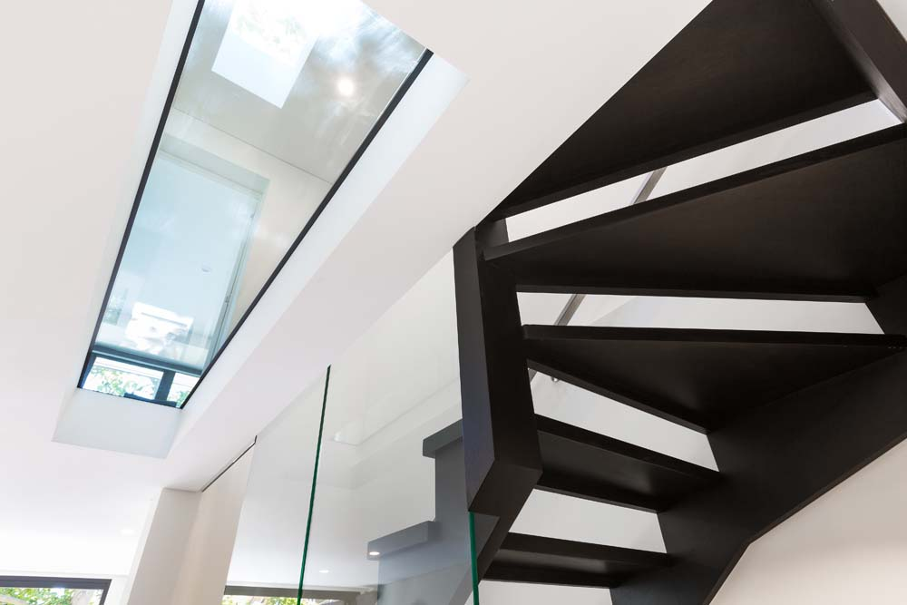 home builders Rose bay Home Renovation - Black contrasting stairway with white walls and glass finishing