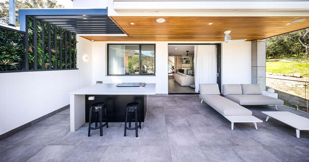 Outside barbeque area with relaxed seating and wooden ceiling - Modern outdoor patio - Home Renovation