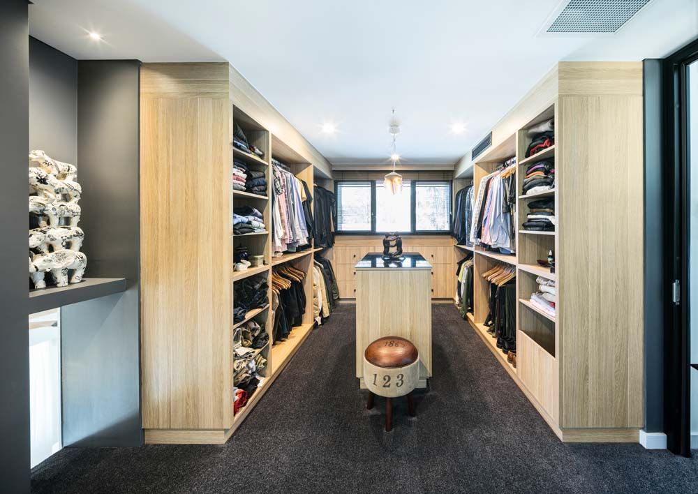 Woronora Home Renovation - walk in wardrobe with wooden finishing and dark colour scheme