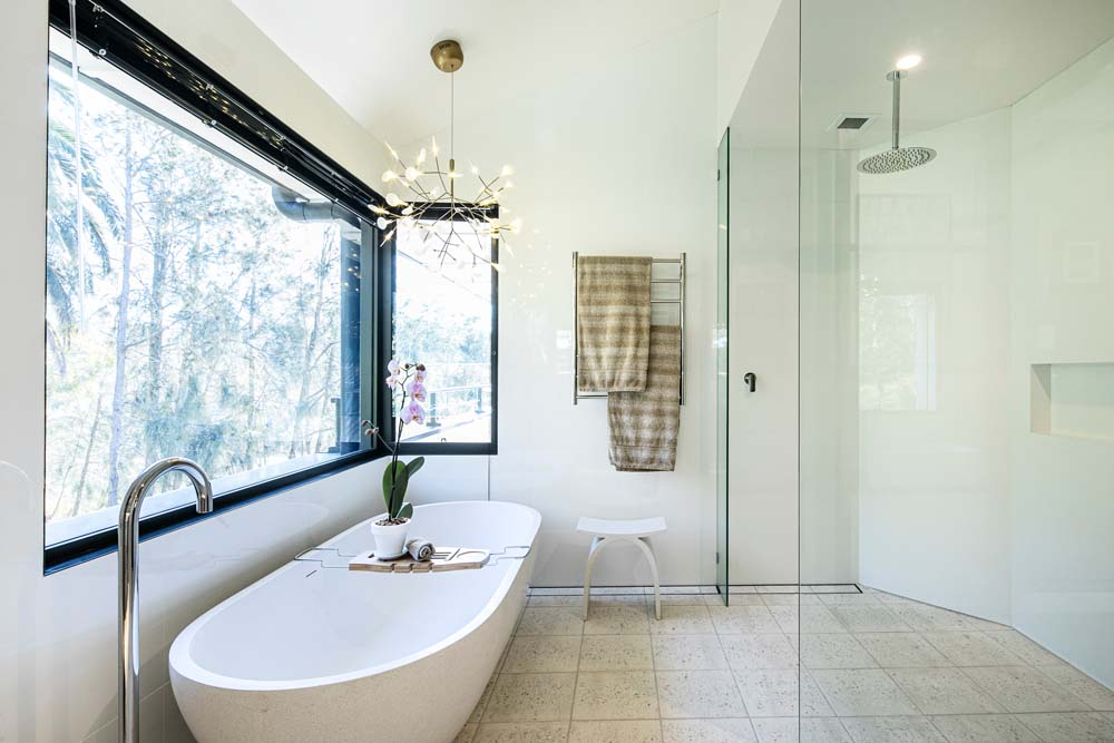 Woronora Home Renovation - Bathroom renovation - White bathtub and shower area with glass divider