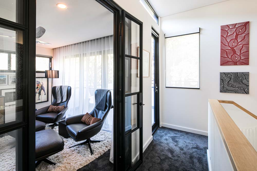 Woronora Home renovation - Inside seating area with white walls, black carpeting and black frame finishing