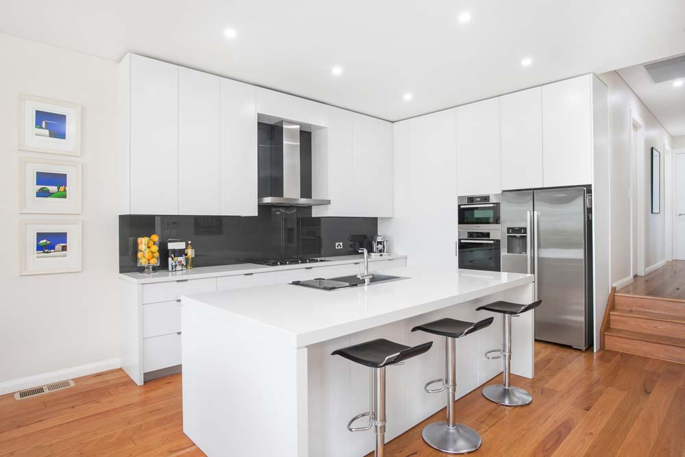 new home builder Ischia Home Renovation - Kitchen renovation - White themed cabnets with black walls and wooden floors