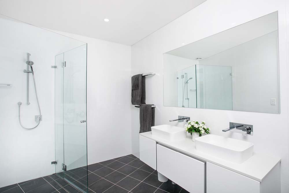 Ischia Bathroom Renovation sydney - Modern Bathroom with white walls and black flooring