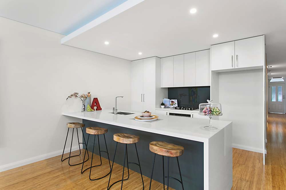 Zetland modern kitchen with white cabinets with wooden seating bar stools