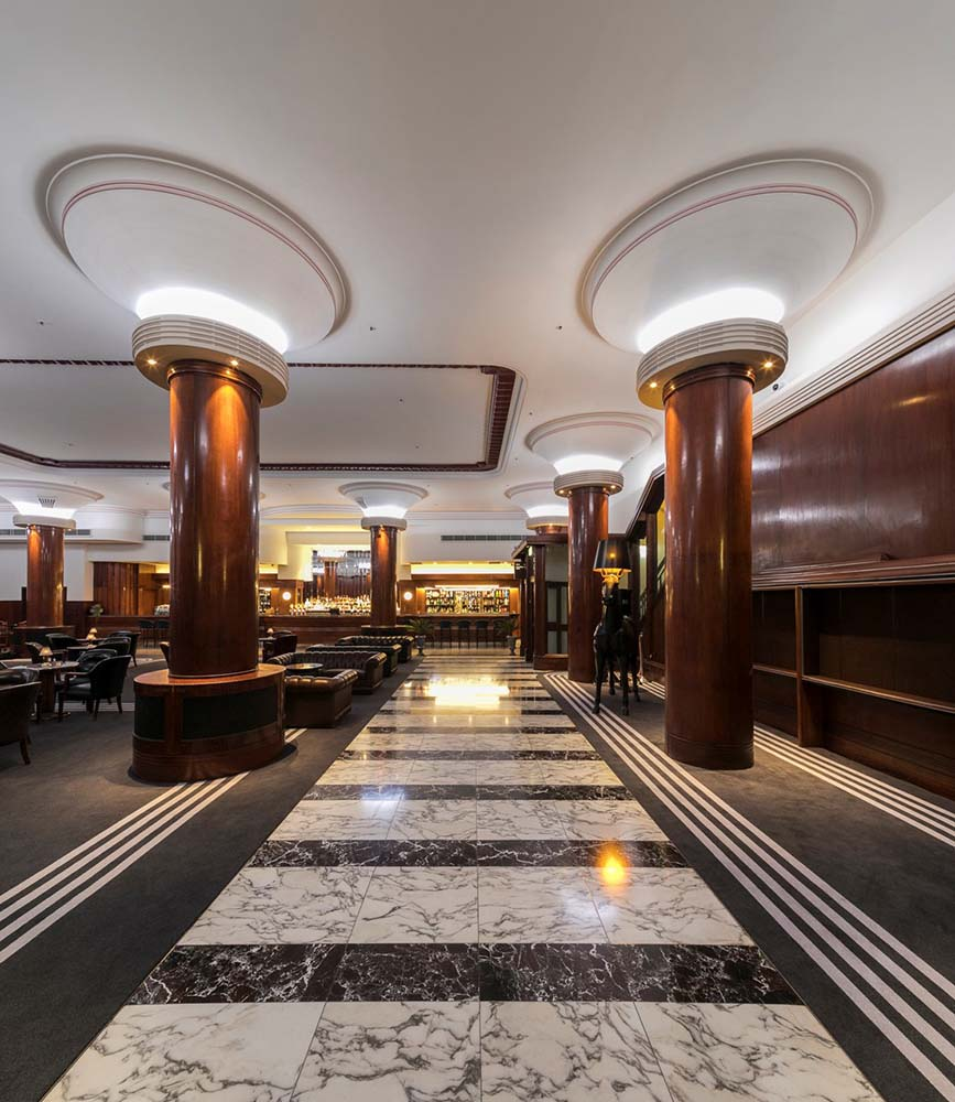 City tattersalls club - Commercial Renovation - Lounge area and hallway to the bar with marble flooring